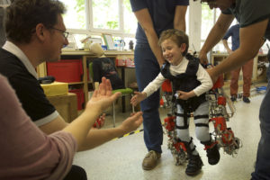 child walking for the first time with the exotrainer exoskeleton